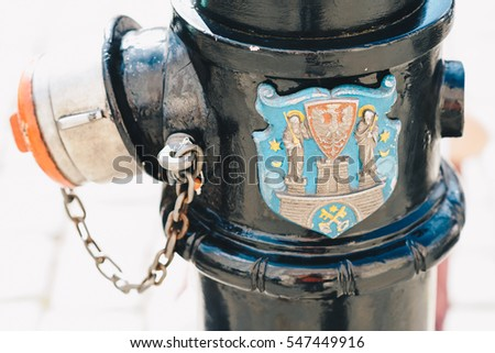 Old fire hydrant with the coat of arms of Poznan; Poland - shallow depth of field