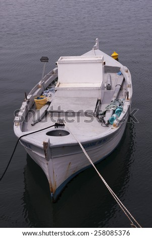 old fishing boat anchored in the harbor - stock photo