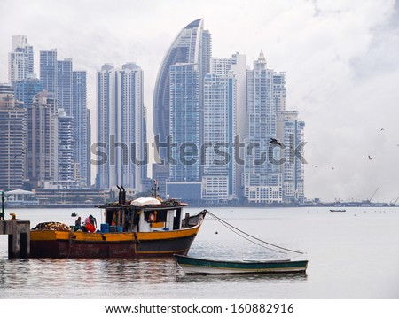 Old fishing boat in foreground with skyscrapers in background, Panama City , Panama, Central America - stock photo