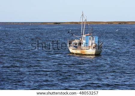 Old fishing boat in the sea - stock photo