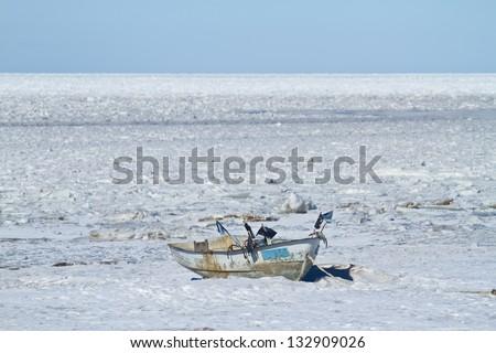 Old fishing boat on a frozen seashore - stock photo