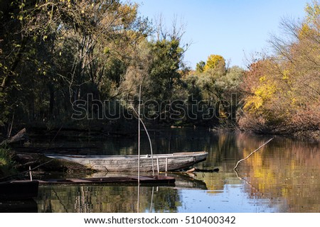 Old fishing boat on the lake in autumn
