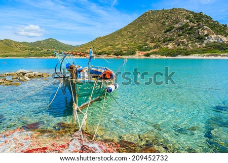 Old fishing boat on turquoise sea water of Punta Molentis bay, Sardinia island, Italy - stock photo
