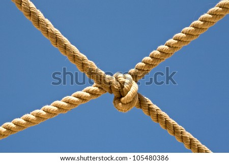 Old fishing boat rope against blue sky - stock photo