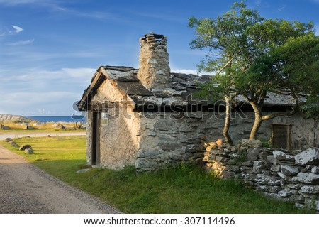 Old fishing cottage on the small fishing place Vitvaers near Ljugarn, island Gotland, Sweden on a clear and bright summer morning. - stock photo