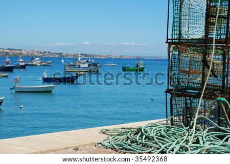 old fishing equipment with harbor background boats in Cascais, Portugal - stock photo