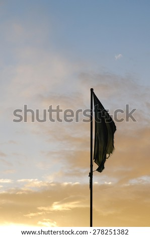old flag at sunset and no wind - stock photo