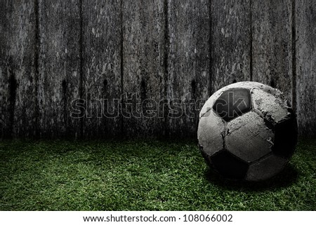 Old football on grass - stock photo
