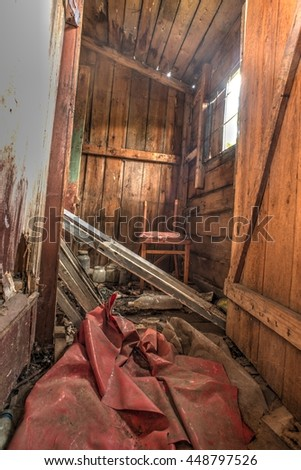 Old forgotten and abandoned home interior in a derelict decaying state with dirt covered floors and bare wooden walls. - stock photo