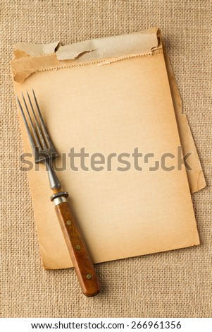 Old fork on yellowed paper - stock photo