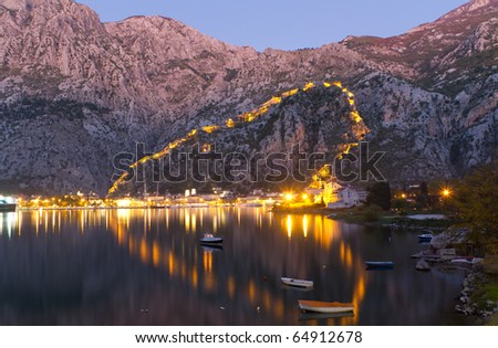 Old Fortress Walls of Kotor, Motenegro Lit Up at Night and Reflecting on the Bay of Kotor - stock photo