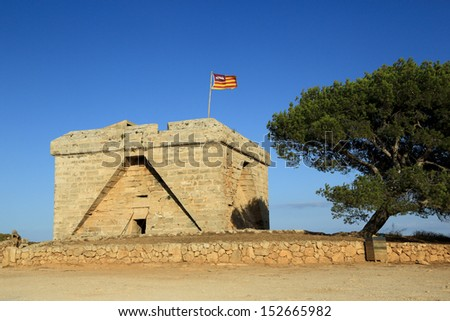 Old fortress with a flag of Mallorca. Spain. - stock photo