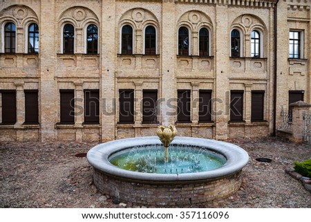 Old fountain and brick house in Vilnius, Lithuania - stock photo