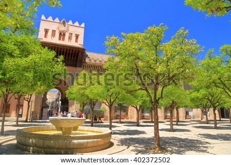 Old fountain in the courtyard of the Cathedral of Saint Mary of the See (Seville Cathedral) with green orange trees in Seville, Andalusia, Spain - stock photo