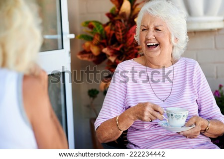 Old friends laughing together and having tea - stock photo