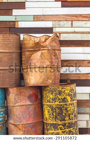old fuel tanks that lay altogether and grunge wooden background - stock photo