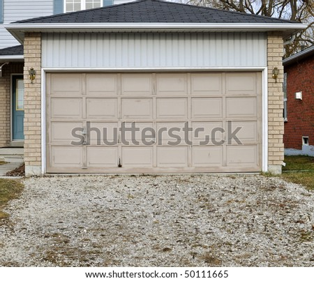 Old garage door with overgrown gravel driveway
