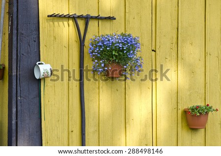 old garden rake and flowerpots with flowers on old wooden wall - stock photo