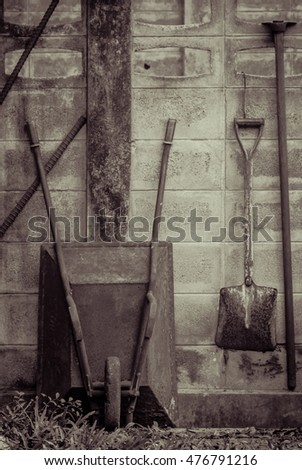 Old garden tool at wall in vintage color style