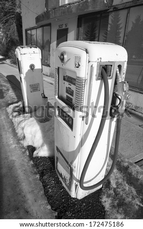 Old gas pumps at an abandoned gas station in black and white - stock photo