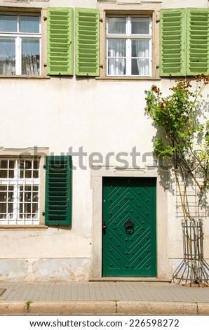 Old german house with green door and shutters, sidewalk in the front.  - stock photo