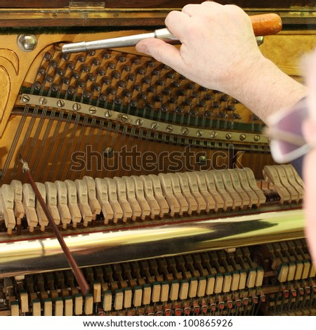 Old german piano during a tuning. Unrecognizable master. - stock photo