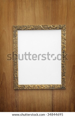 Old gilded photo frame with blank paper on wooden wall - stock photo