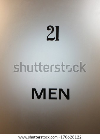 Old glass door to a men's washroom - stock photo