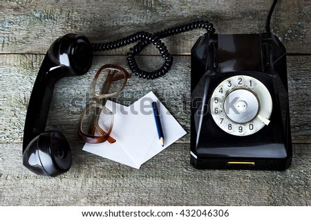Old glasses with sheet for notes, pencil and black vintage phone on wooden background   close-up, top view, pick up the phone - stock photo