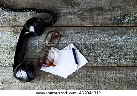Old glasses with sheet for notes, pencil and black vintage phone on wooden background   close-up, top view, pick up the phone, copyspace - stock photo