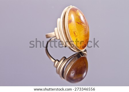 Old gold ring with inset amber on the reflecting surface - stock photo
