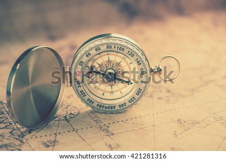 Old  gold vintage compass on vintage map:Heading south;vintage tone style - stock photo