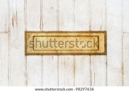Old golden mailbox in the white wooden door - stock photo
