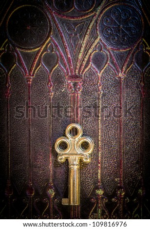 Old golden metal key lying on a decorated ancient book cover - stock photo
