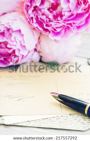 old golden quill pen and antique letters with peonies flowers - stock photo