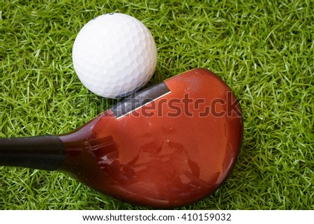 Old golf club and golf ball on green grass background.Outdoor sport concept. - stock photo