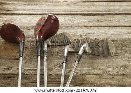 Old golf clubs on rough wooden surface - stock photo