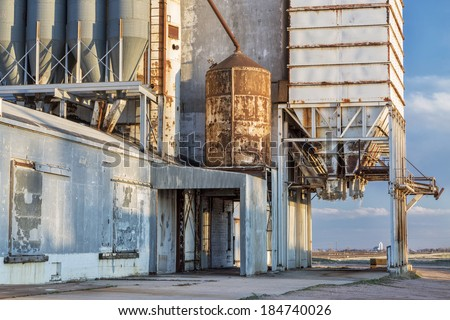 old grain elevator with pipes, ducts, ladders and chutes, a distant rural landscape of northern Colorado - stock photo