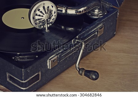 old gramophone with vinyl records, stands on a table - stock photo