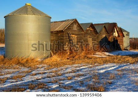 old granaries in a snowy field - stock photo