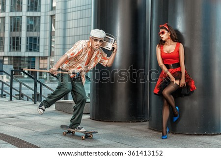 Old grandfather rushes on a skateboard. He had a stick in his hand for the elderly. - stock photo