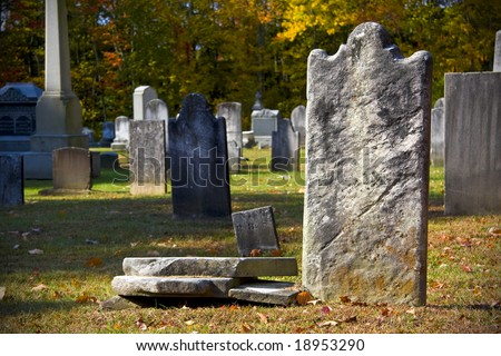 Old granite blank headstone in creepy churchyard during autumn season - stock photo