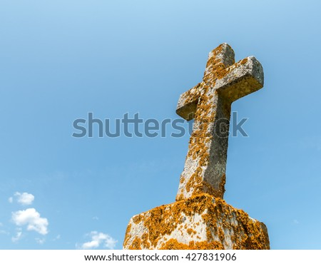 Old grave marker cross. It is covered with moss and lichens. About half the cross is covered with yellow growth. The cross is starting to fall over. Focus is on the cross. There is room for text. - stock photo