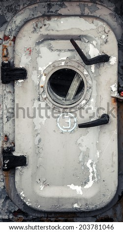 Old gray ship door with porthole and handles - stock photo
