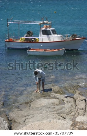 Old Greek fisherman and his boat - stock photo