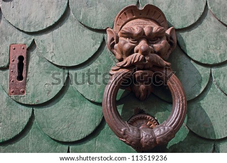 Old green door in Pisa, Italy with am aged rusty handle and key hole. - stock photo