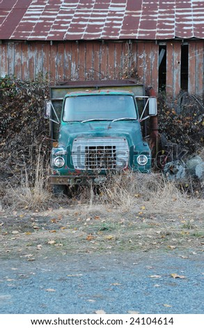 Old green farm truck overgrown with shrubs - stock photo