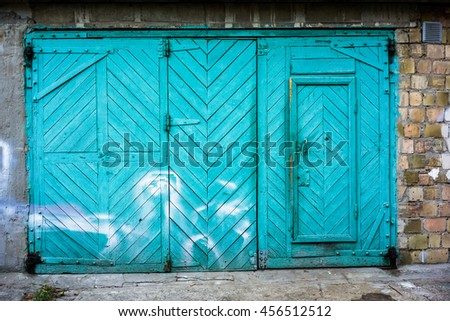 Old green wooden garage gate with brick wall