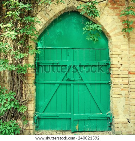 Old green wooden gate in the rural brick wall, square toned image - stock photo