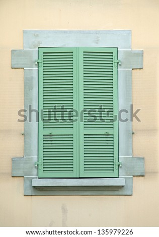 Old Green Wooden shutters on building with stone facade.